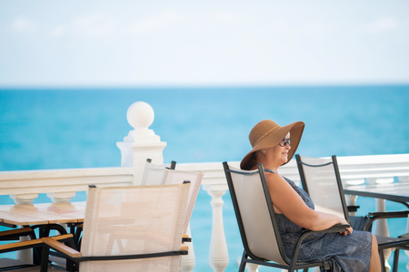 An elderly woman sitting in the outdoor restaurant, sea at the background. Old lady wearing straw hat and sunglasses Stock Photo