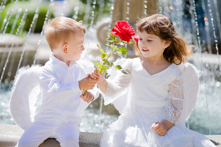 Adorable toddler boy and girl in angel costumes sitting together, boy giving red rose to the girl. Saint Valentines day. First love. Angelic children