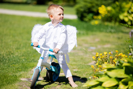 Toddler boy wearing angel wings riding a balance bike (run bike), learning to keep balance on a training bicycle in the garden. Activity for children Фото со стока