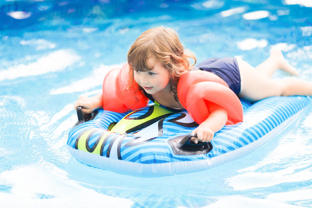 Adorable little girl with inflatable over-sleeves floats swiming in the pool, lying at the inflatable mattress. Little swimmer Reklamní fotografie