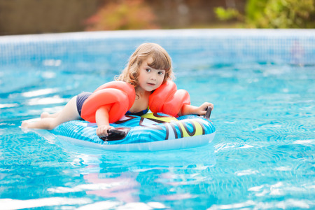 Adorable little girl with inflatable over-sleeves floats swiming in the pool, lying at the inflatable mattress. Little swimmer