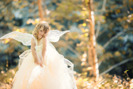 Fairy tale consept. Little toddler girl wearing beautiful princess dress with fairy wings in the forest Stock Photo