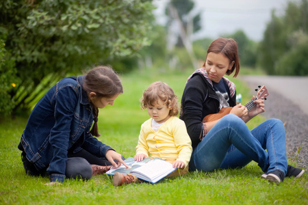 Little girl learning read and playing musical instruments outdoors, early all-round development