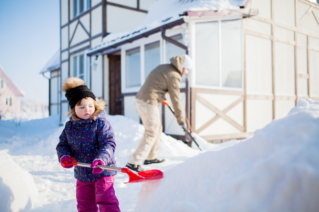 Little girl with and her father working outdoors with a snow shovel, winter day. 스톡 콘텐츠