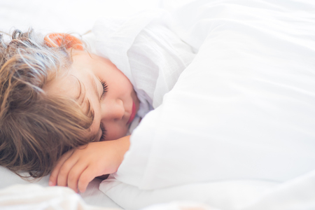 Adorable little girl lying in the bed and sleeping in the early morning, healthy sleep, easy wake up.