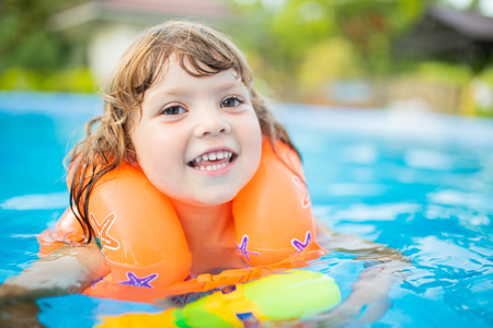 Adorable little girl with inflatable life vest having fun, learning to swim in the pool. Banco de Imagens