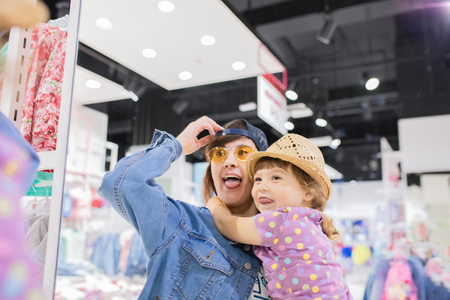 Mother ang her cute little daughter having fun together at the clothes store, looking at the mirror, trying on new clothes