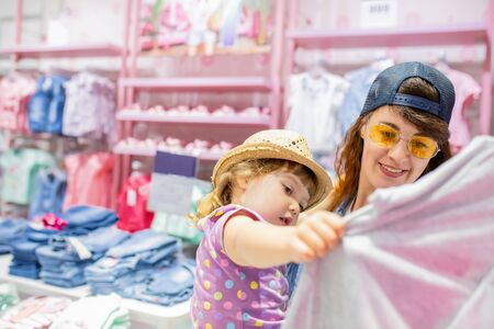 Mother and her cute little daughter having fun together at the clothes store, buying clothes