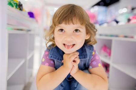 Adorable smiling happy little girl having fun at the clothes store, sale concept