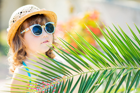 Adorable little girl wearing sunglasses and straw hat, walking at the tropical resort, hiding behind the palm three at the sunny summer day