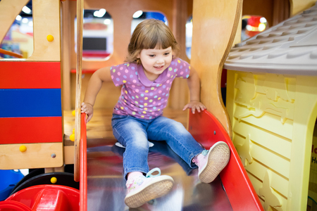 Cute happy toddler girl at childrens slide on a playground or kindergarten