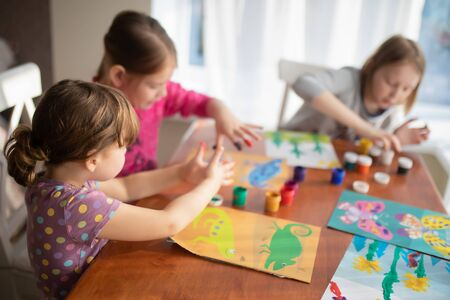 Threesisters little girls drawing with fingers on paper at home. Play, fun, childhood. Montessori school