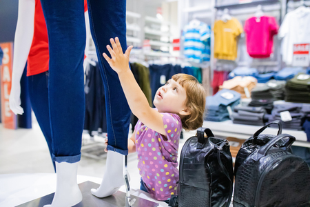 Adorable toddler girl in baby apparel store, buying clothes
