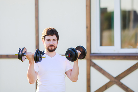 Young man lifting dumbbells putdoors. Active healthy life Fitness. Sport 版權商用圖片
