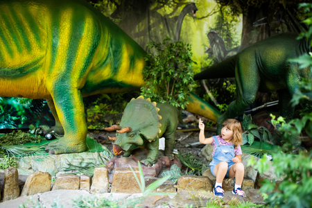 Little girl watches a dinosaur sculpture in amusement park at summer. Kid loving dinosaurs