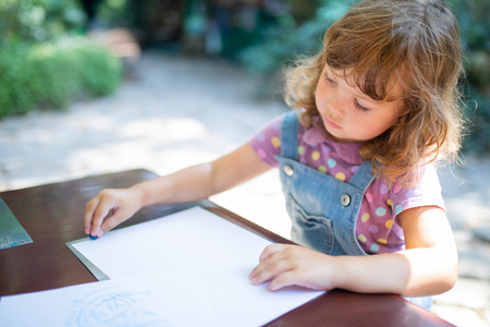 Adorable little girl drawing with chalk pencils outdoors. Summer leisure. Talantes kids, early art education.