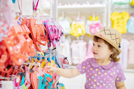 Adorable toddler girl in baby apparel store, buying slippers for summer 版權商用圖片