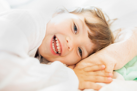Adorable little girl lying in the bed and smiling in the early morning, healthy sleep, easy wake up 版權商用圖片