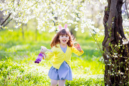 Adorable little girl playing in blooming  tree garden on Easter egg hunt, running and smiling. 版權商用圖片