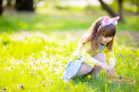 Adorable little girl playing in the garden on Easter egg hunt, searching eggs in the grass at spring April day.