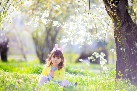 Cute little girl with curly hair wearing bunny ears and summer dress having fun during Easter egg hunt relaxing sitting at the grass in the blooming garden on a sunny spring day. 版權商用圖片