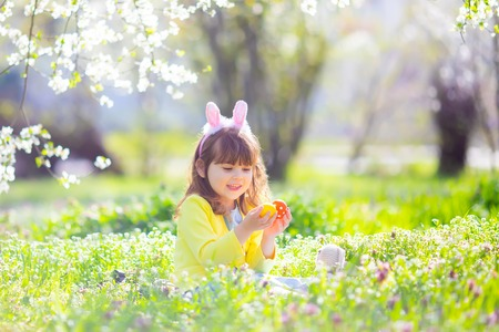 Cute little girl with curly hair wearing bunny ears and summer dress having fun during Easter egg hunt Imagens