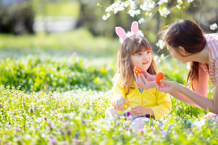 Cute little girl with curly hair wearing bunny ears and summer dress having fun with her young mother 版權商用圖片
