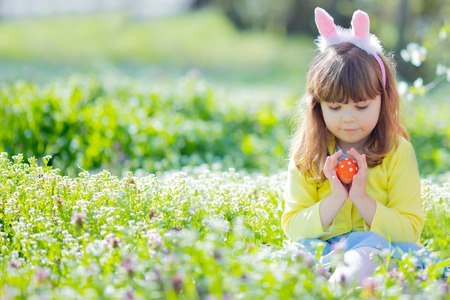 Cute little girl with curly hair wearing bunny ears and summer dress having fun during Easter egg hunt Foto de archivo