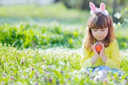 Nettes kleines Mädchen mit lockigem Haar, das Hasenohren und Sommerkleid trägt und Spaß bei der Ostereiersuche hat Standard-Bild