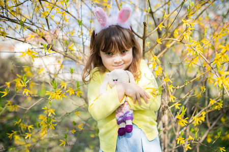 Evil child wearing bunny ears, girl holding rabbit toy in the spring blossom garden.