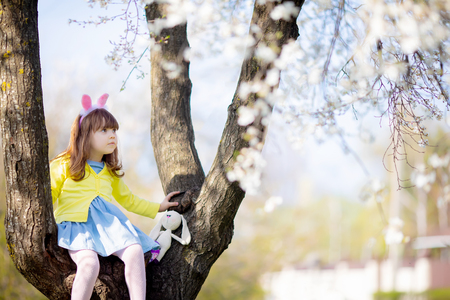 Adorable little funny bunny girl, having fun, sitting at the blooming three at sunny spring day. Easter time.