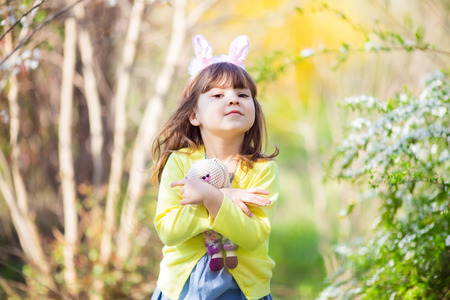 Adorable little funny bunny girl with rabbit toy, outdoors, spring, Easter.