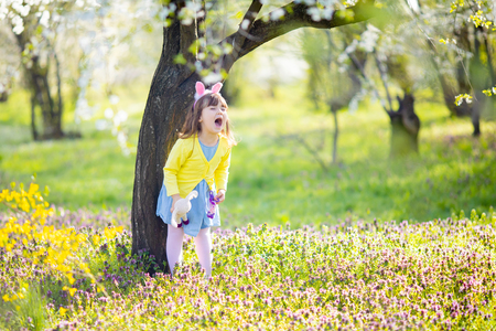 Unhappy little sad and angry naughty crying bunny girl holding rabbit toy in the spring blossom garden during Easter egg hunt
