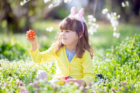 Bambina carina con i capelli ricci che indossa orecchie da coniglio e abiti estivi che si divertono durante la caccia alle uova di Pasqua