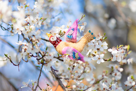 Beautiful handmade Easter decorations: colorful bird hanging on a blooming cherry tree at spring Easter day.