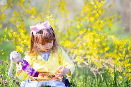 Cute little girl with curly hair wearing bunny ears and summer dress having fun during Easter egg hunt
