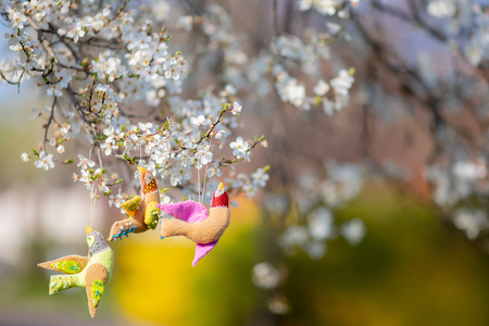 Beautiful hand made Easter decorations: colorful birds hanging on a blooming cherry tree at spring Easter day.