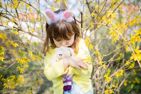 Unhappy little sad bunny girl standing alone, holding rabbit toy toy in the spring blossom garden. Easter time.