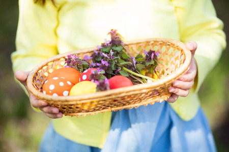 Close up of colorful Easter eggs in a basket at childs hands