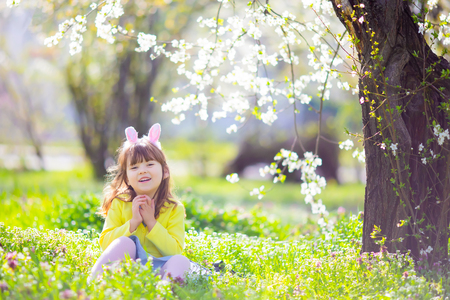 Cute little girl with curly hair wearing bunny ears and summer dress having fun during Easter egg hunt relaxing sitting at the grass in the blooming garden on a sunny spring day