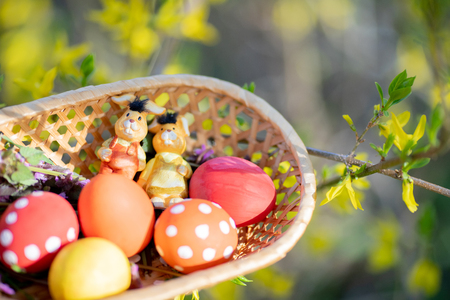 Close up of colorful hand made Easter eggs and little bunnies figurines in a basket outdoors, Easter decorations, cherry blossom.