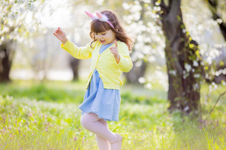 Adorable little girl playing in the cherry blooming garden on Easter egg hunt, searching eggs in the grass at spring April day.