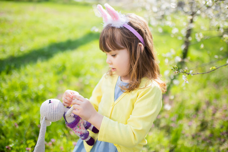 Adorable little funny bunny girl holding rabbit toy in the spring blossom garden. Easter time.