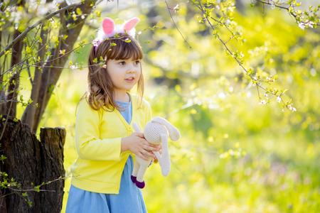 Adorable little funny bunny girl holding rabbit toy in the spring blossom garden. Easter time