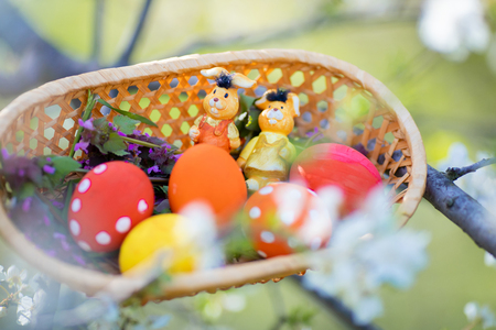Close-up of colorful hand made Easter eggs and little bunnies figurines in a basket outdoors, Easter decorations, cherry blossom.