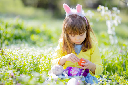 Cute little girl with curly hair wearing bunny ears and summer dress having fun during Easter egg hunt relaxing sitting at the grass and playing with colorful Easter eggs in the blooming garden on a sunny spring day. 版權商用圖片