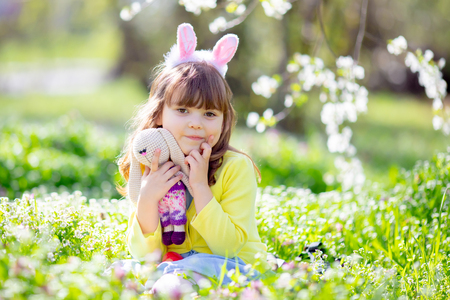 Cute little girl with curly hair wearing bunny ears and summer dress relaxing sitting at the grass with rabbit toy in the blooming garden on a sunny spring day during Easter egg hunt.