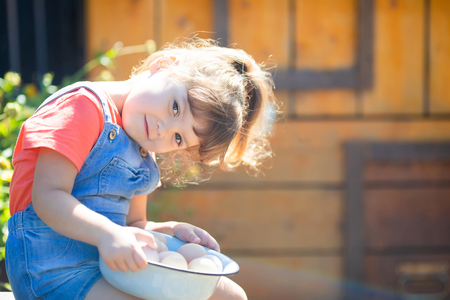 Adorable little girl holding basket full of white and brown raw eggs, wooden chicken coop