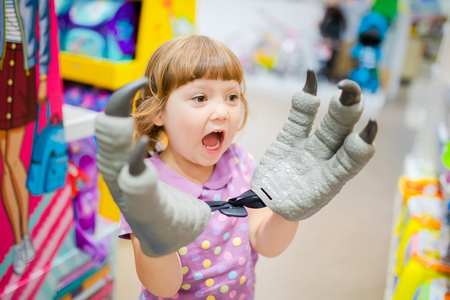 Little kid girl having fun at the children shop, choosing toys, lifestyle
