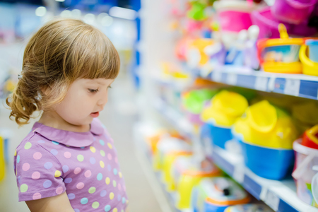 Little kid girl at the children shop, choosing toys, lifestyle